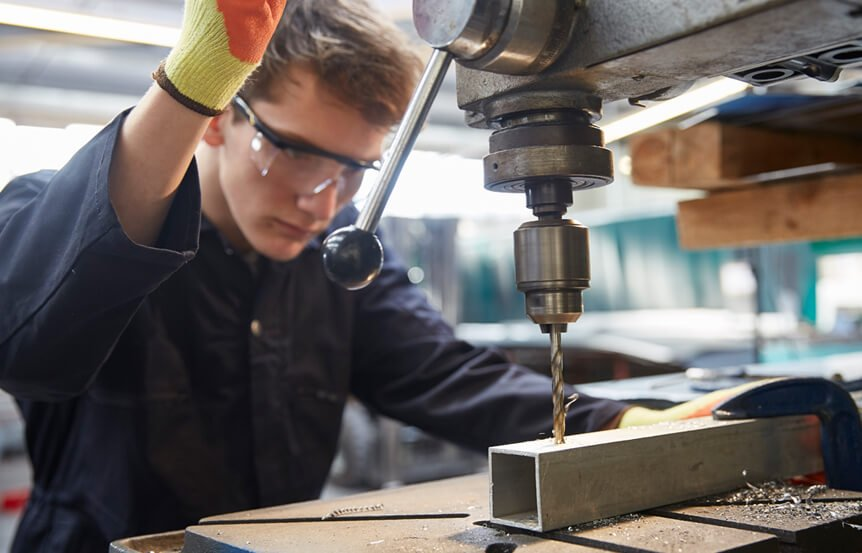 man with safety glasses using a drill